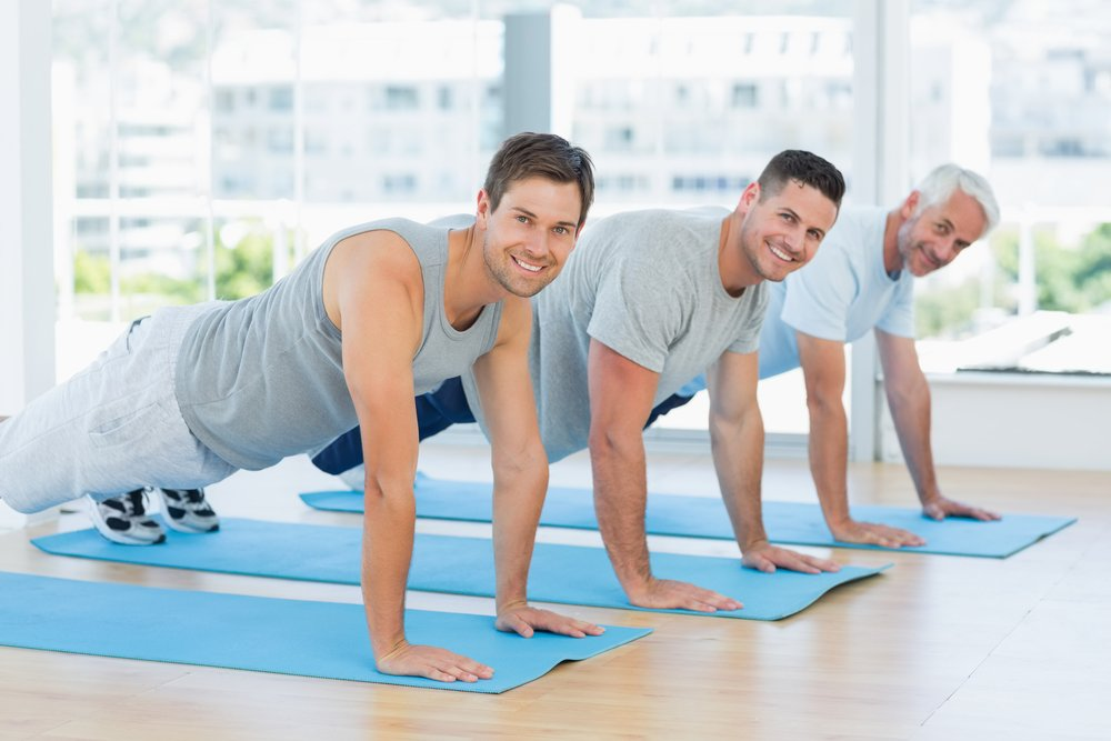Three men plank at a yoga studio, pleased with how their sperm retrieval procedures went at PCRM's fertility clinic
