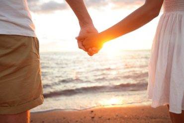 A couple holds hands at the beach during sunset